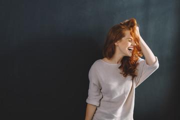 Fun young woman enjoying a good hearty laugh