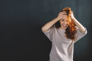 Amused young redhead woman laughing