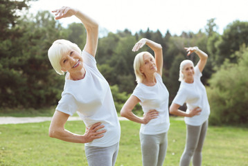 Staying fit. Happy positive aged woman smiling and doing the bending exercise while enjoying it