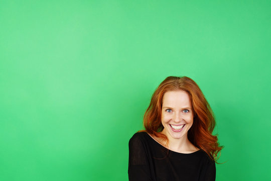 Young cheerful woman against green background
