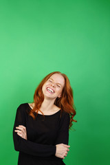 Young woman laughing against green background