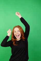 Young enthusiastic woman against green background