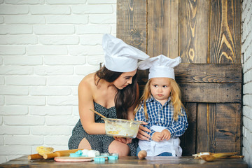 Sad child boy with woman in kitchen