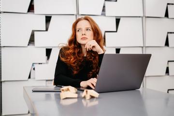 Pretty redhead woman sitting daydreaming at work