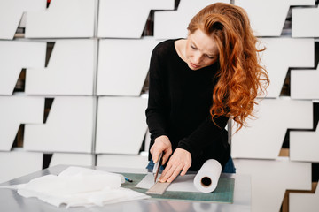 Young woman cutting a roll of paper with a blade