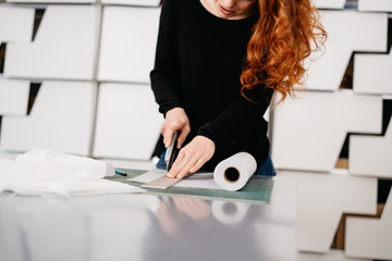 Creative young woman cutting paper with a blade