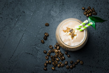 Creamy coffee breakfast smoothie and coffee beans on dark concrete background. Top view, space for text, close up, selective focus.