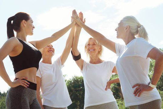 We are the team. Joyful nice active women looking at each other and giving a high five while being ready to train