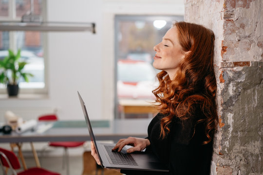 Attractive redhead woman standing daydreaming