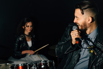Wedding in the style of rock. Guys with stylish leather jackets. It's a rock'n'roll baby! Sweet couple in a music studio. The bride plays the drums, and the groom sings.