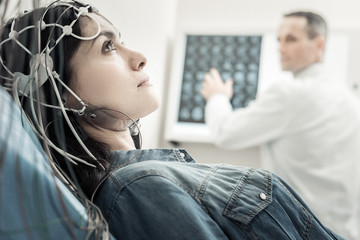 Electro scanning. Nice beautiful young woman lying on the bed and wearing wires while undergoing electro scanning