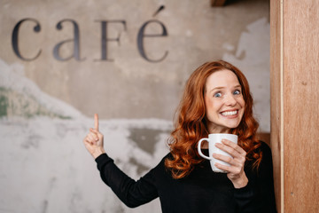 Portrait of cheerful redhead woman drinking coffee