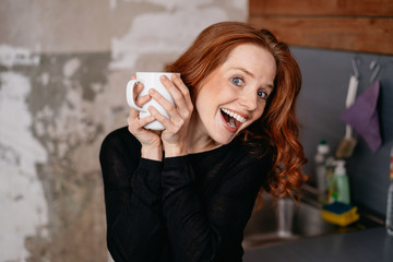 Smiling young woman holding cup of coffee