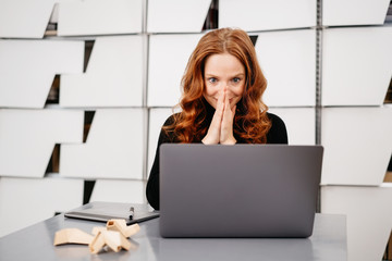 Excited young businesswoman looking at her laptop