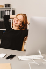 Happy woman sitting at desk in a modern office