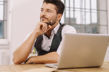 Thoughtful man sitting in front of laptop