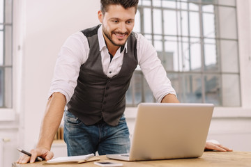 Smiling man working with laptop at office