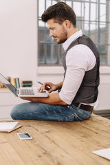 Businessman sitting perched on his desk