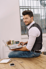 Young smiling man with laptop in office