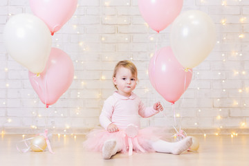 birthday party concept - little girl over brick wall background with lights and balloons