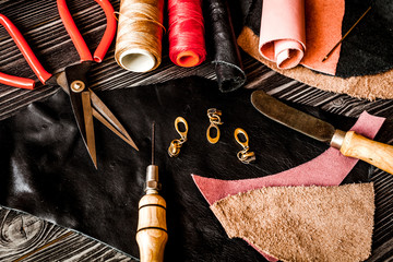 Instruments in leather shop on dark wooden background top view