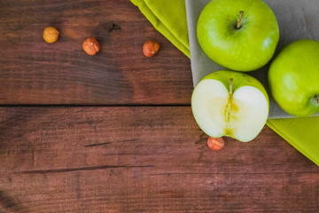 Green apples on tablecloth. Dark wooden background. Apple cut. Top view.