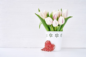White tulips bouquet in white vase decorated with red heart. Valentines Day, Wedding concept. Copy space