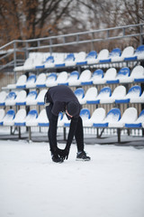 Picture of sports man doing stretching at stadium