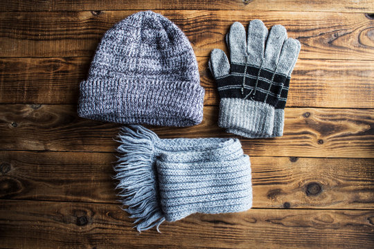 grey winter hat gloves scarf on a wooden bacground