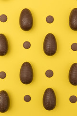 Chocolate easter eggs on a bright yellow background. Easter holiday concept