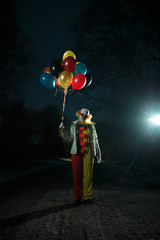 Photo of clown with balls in hands at night