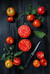 Beautiful tomatoes on the dark wooden table