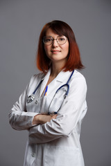 Image of smiling female doctor in white lab coat and with phonendoscope in glasses