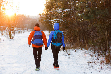 Romantic photo from back of man and woman with backpacks in winter forest