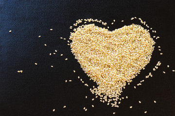 White sesame seeds arranged in heart shape on black background. Copy space.