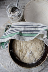 dough rising in large brown bowl covered with tea towel top view