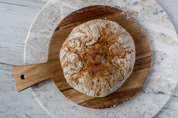 round baked bread on round wooden platter sitting on round marble table top view