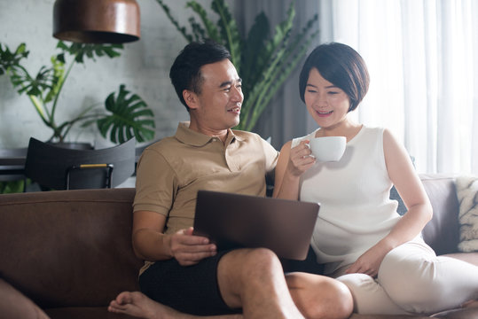 Happy Asian couple looking at the computer together at home.