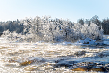 Sunrise river in a cold winter landscape with snow and frost.