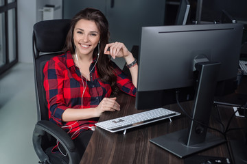 Successful young woman sitting at table in office, working on her desktop.