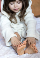 Little child applying cream and lotion to her legs after bathing at home.