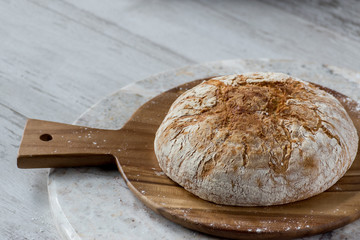 round baked bread on round wooden platter sitting on round marble table