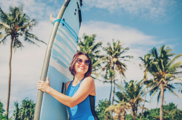Happy smiling woman with surf board posing on tropical beach