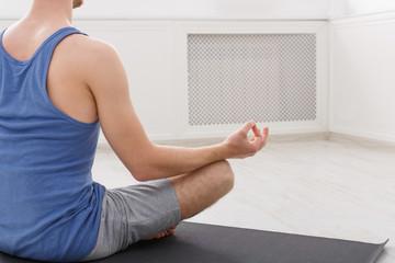 Unrecognizable man training yoga in lotus pose, copy space