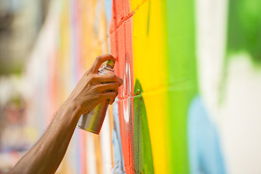 hand spraying  to paint the street art on wall.