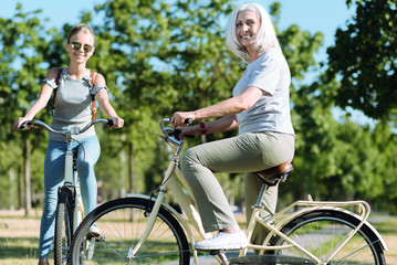 Active sport. Joyful positive aged woman riding a bike and smiling while leading healthy lifestyle