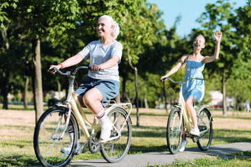 Healthy lifestyle. Delighted positive elderly woman riding a bike and being in a positive mood while leading healthy lifestyle