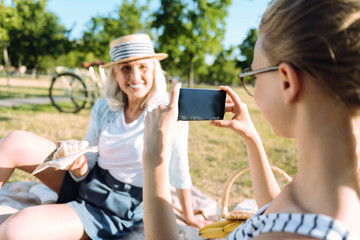 Young photographer. Cute nice positive girl looking at her grandmother and taking photos while using her smartphone