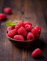 Ripe sweet raspberries in bowl on wooden table.