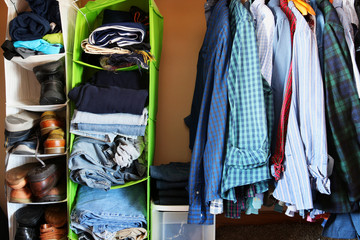 Private house closet with well organized casual man clothes.Man wardrobe with variety of shirts hung on hangers, shoes and pile of jumper, jeans and pants lain in a storage organizers pocket shelves.